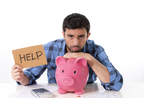 Young Attractive Broke Man In Stress Feeling Sad Hugging Empty Piggy Bank With Calculator Accounting His Bad Financial Situation Asking For Help In A  Billboard Sign Wearing Casual Shirt Isolated On White Background
