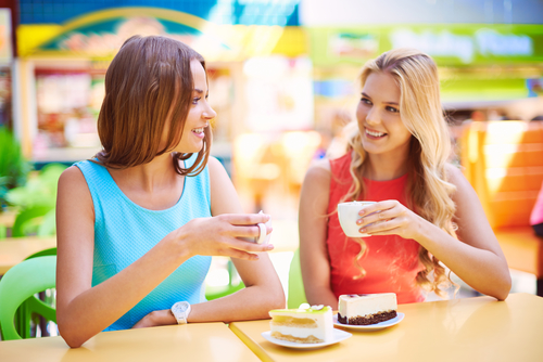 Portrait Of Two Girls Having Cheesecakes With Coffee In Cafe