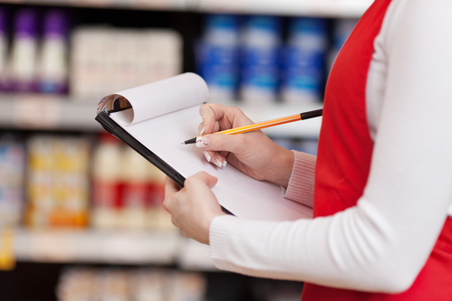 Midsection Of Saleswoman Writing On Clipboard In Grocery Store