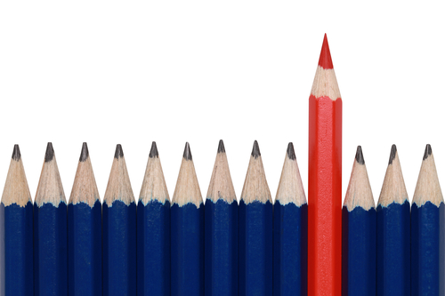 Blue Pencils And One Red Crayon Standing Out From The Crowd. Isolated On White.