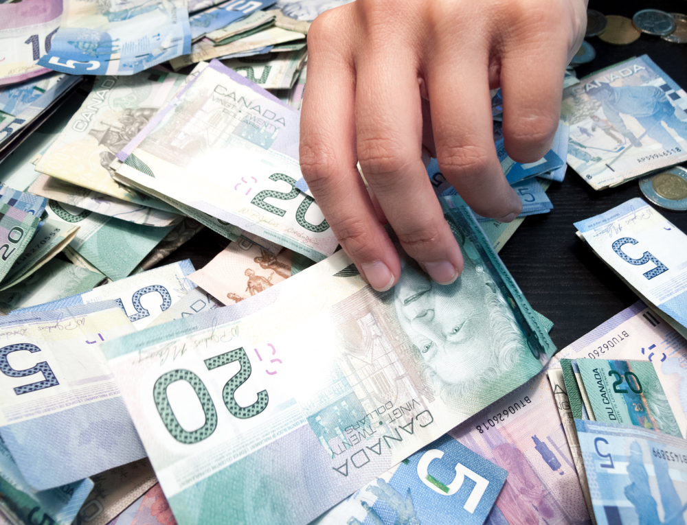 Person's Hands Picking Twenty Canadian Dollar Bill From Heap Of Paper Currency