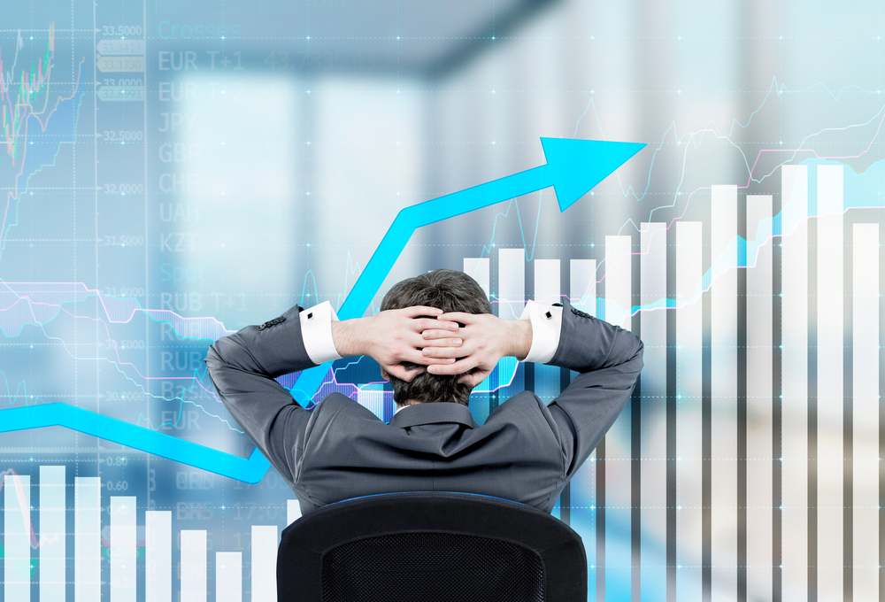Relaxing Businessman Sitting On The Chair With Hands On The Back Of His Head. Image Of Semi-transparent Graphs In Front. Back View. Blurred Office At The Background. A Concept Of Forex Trading.