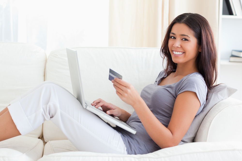 Young Woman Smiling Into Camera With Credit Card In Hands In Livingroom