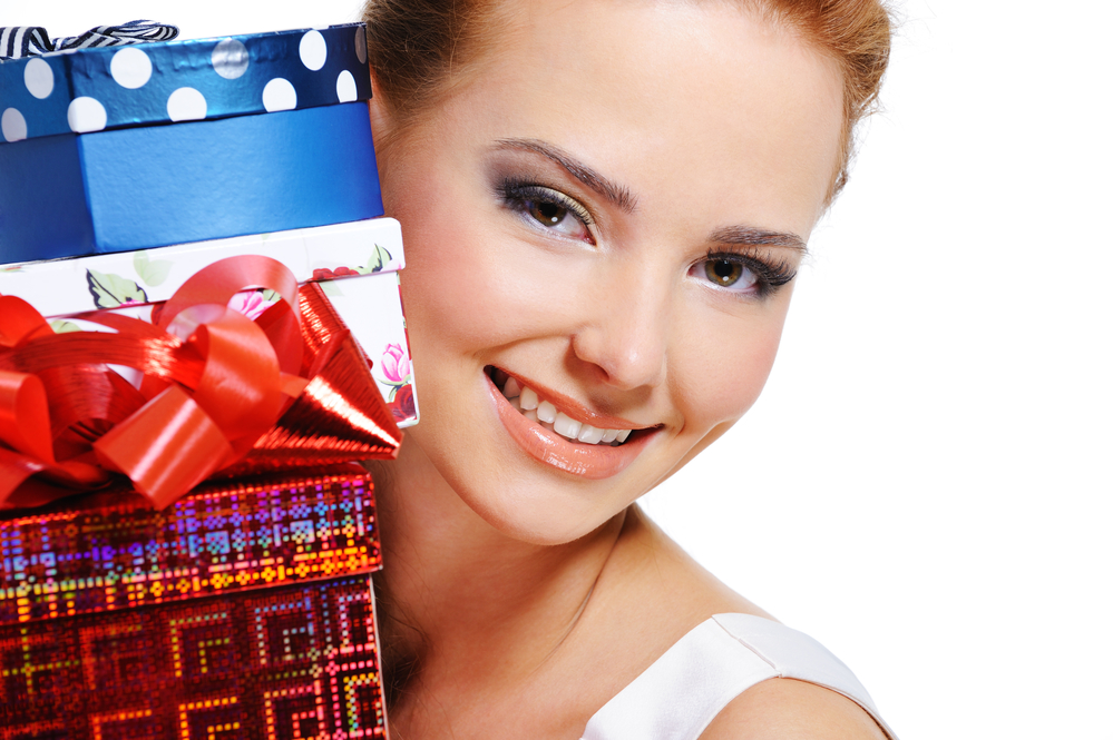 Close-up face of a pretty smiling girl with the many presents over white background